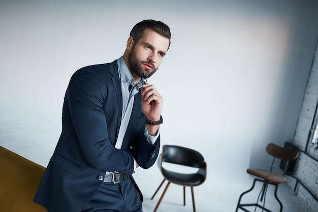 Раньше выглядел идеально красивый молодой бизнесмен смотрит в сторону, стоя в своем современном