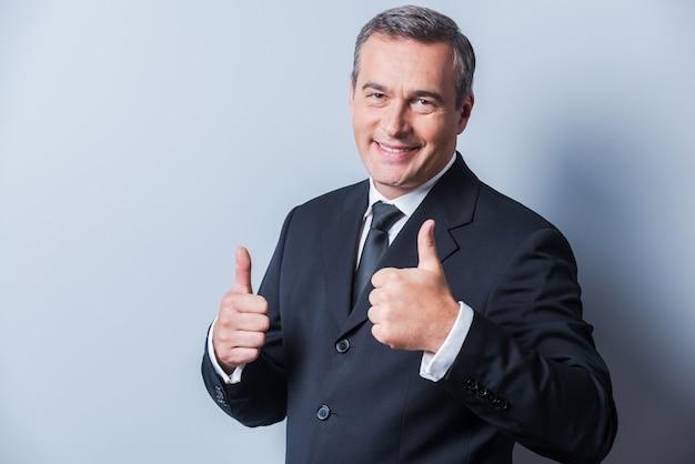 성공에 익숙합니다. 회색 배경에 서서 엄지손가락을 치켜들고 웃고 있는 정장 차림의 자신감 있는 성숙한 남자