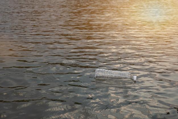 Пластиковая бутылка для использованных отходов, плавающая на воде в канале экологичный подход экология