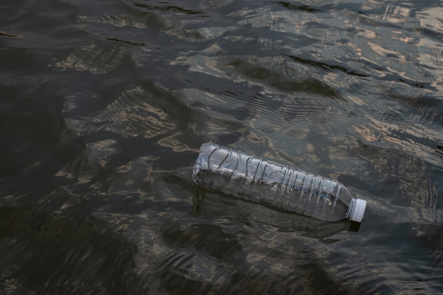 Использованная пластиковая бутылка для отходов, плавающая на воде в канале