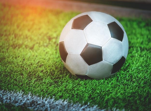 トレーニングピッチのクローズアップショットで使用された使い古された古典的な黒と白のサッカーサッカーボール。