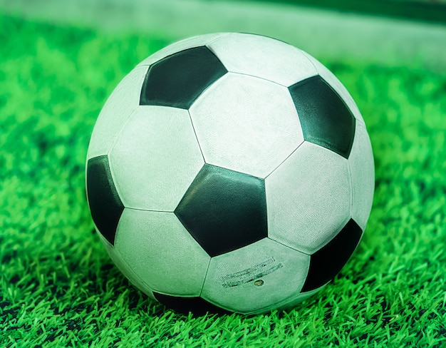 Used weared out classic black and white football soccer ball on training pitch closed up shot.