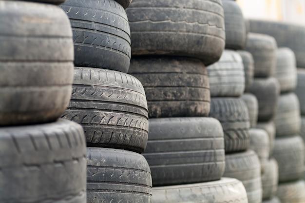 Старые колесные шины уложены штабелями и готовы к переработке.