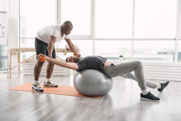 유용한 활동. 훈련을 즐기면서 의료 공에 누워 즐거운 행복한 사람
