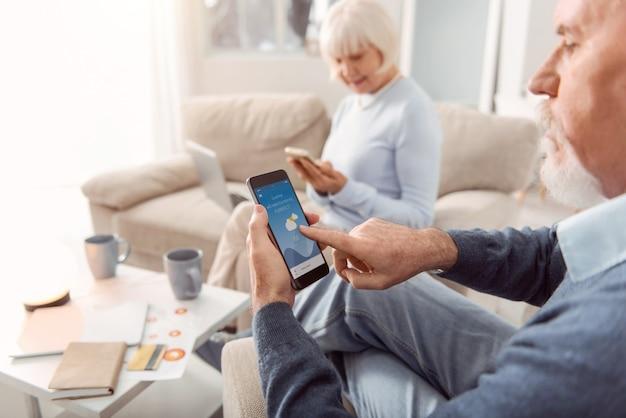 便利なアプリ。居間の肘掛け椅子に座って、電話のアプリケーションで天気予報をチェックしているひげを生やした老人に焦点を当てています