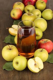 木製のテーブルの上にリンゴが周りにある便利なリンゴジュース