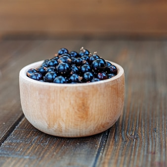 Useful berry. black currants in a wooden bowl. square.