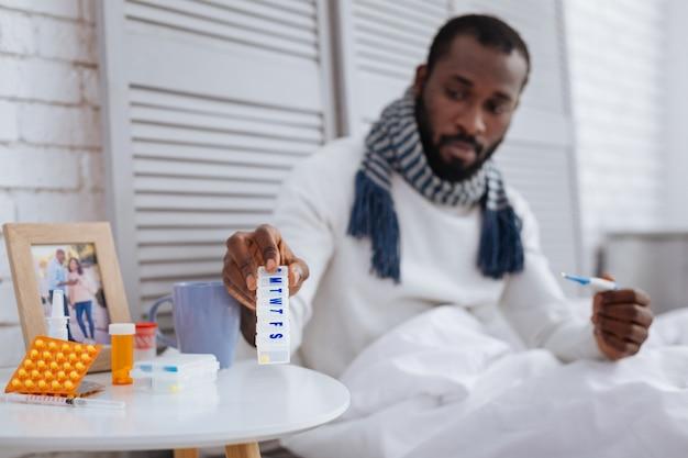 유용한 상자. 그의 왼손에 온도계를 들고 테이블에 알약 상자를 두는 세심한 진정 아픈 남자