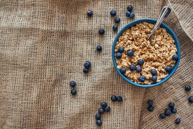 便利な朝食。ブルーベリー、孤立したボウルにオーツ麦と健康的で便利な朝食用シリアルの上面図。朝のヘルシーなおやつや朝食。ミューズリーの金属スプーン