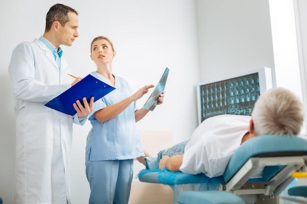Полезное сотрудничество. профессиональные милые умные врачи разговаривают друг с другом и делятся своими идеями, работая вместе