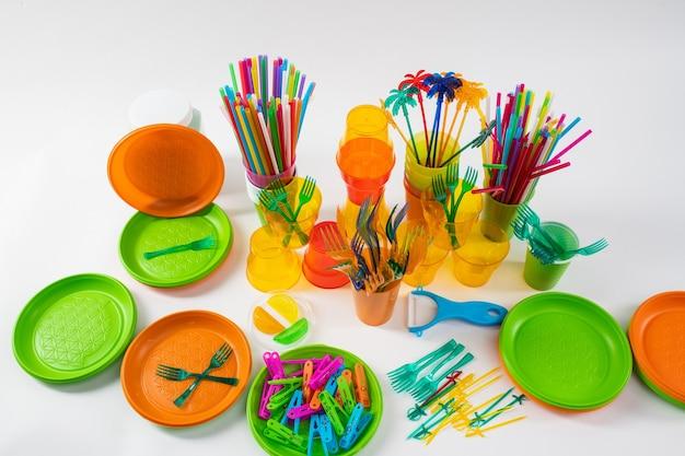 便利な使い捨てのもの。反プラスチックキャンペーンの一環として、フォークとストローで横になっているカラフルなプレートと明るいピン