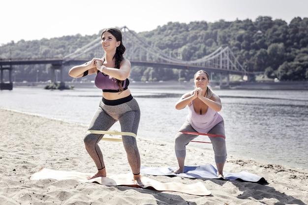 유용한 운동. 야외 운동을하면서 탄성 밴드로 윗몸 일으키기를하는 좋은 여성
