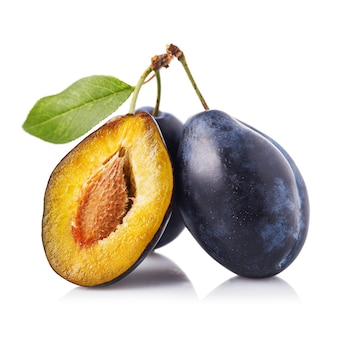Полезные плоды три спелых чернослива, изолированные на белом фоне