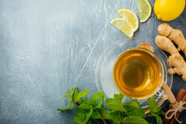 コンクリートブルーの透明なカップにミント、レモン、砂糖を入れた便利なジンジャーティー。