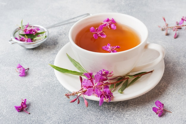 Useful herbal tea from fermented leaves fireweed on grey surface.