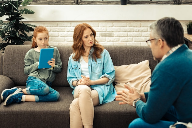 Useful information. beautiful serious woman sitting on the sofa while listening to psychologist advice about her daughter