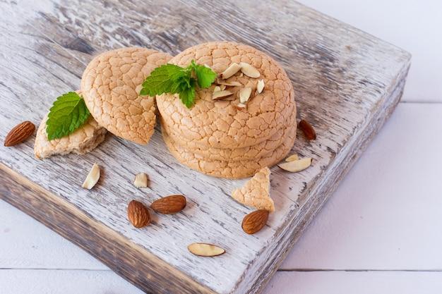 白い木製の背景に白い木製のまな板に積み重ねられたアーモンド粉からの便利な四旬節のクッキー。セレクティブフォーカス。