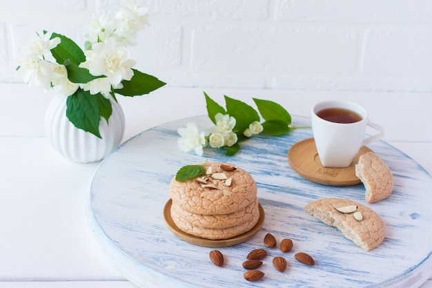 Useful lenten cookies from almond flour stacked on white wooden background wuth cup of jasmine tea. selective focus