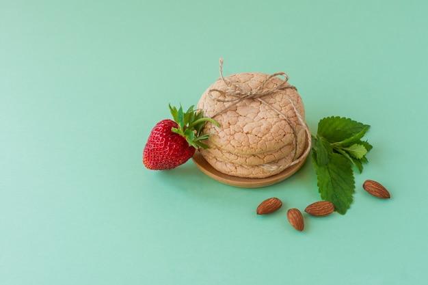 녹색 배경에 견과류와 딸기가 있는 아몬드 가루로 만든 유용한 사순절 쿠키. 선택적 초점.