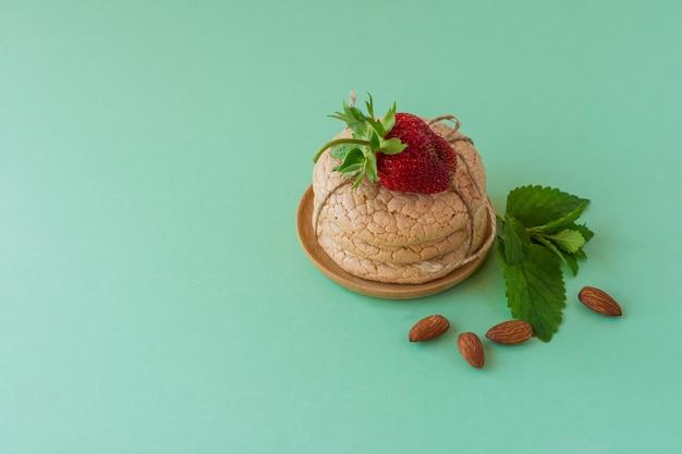 緑の背景にナッツとイチゴのアーモンド粉からの便利な四旬節のクッキー。セレクティブフォーカス。
