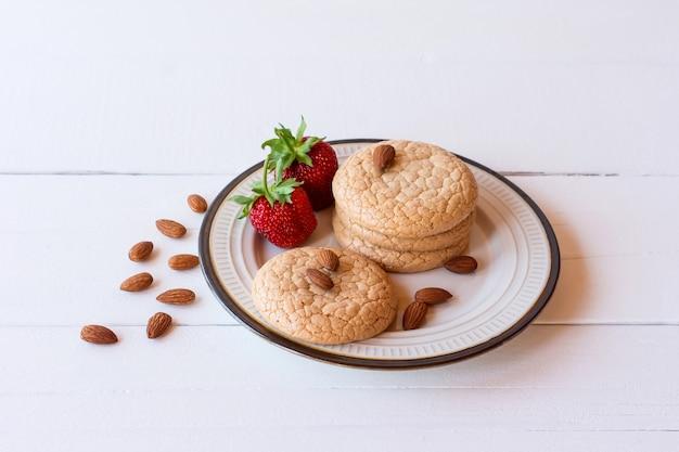 素朴な木製の背景にイチゴとアーモンド粉からの便利な四旬節のクッキー。セレクティブフォーカス。