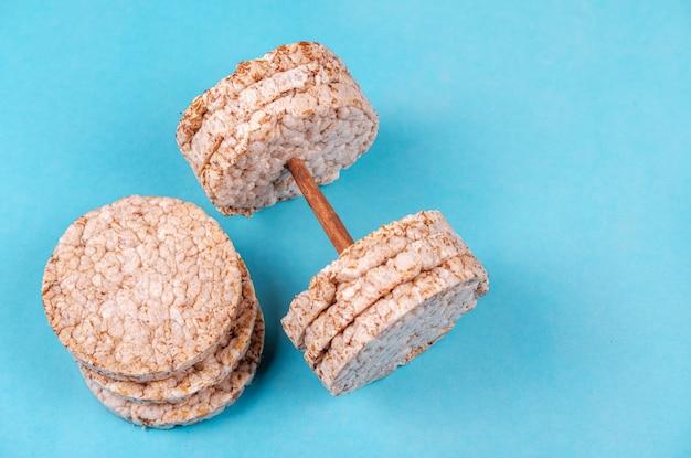 青い背景にダンベルの形をした丸い形の発芽穀物の便利なパン。フィットネスのためのビーガンパン。スポーツと栄養の概念