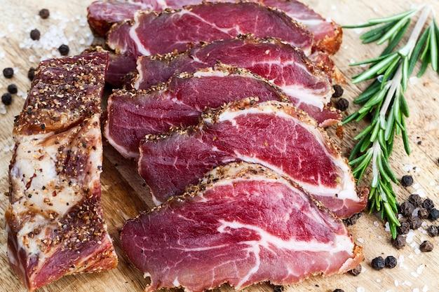 육류 생산 공장에서 만드는 유용한 육류 제품, 신선한 녹색 허브와 향신료를 곁들인 슬라이스 고기 클로즈업, 돼지 고기