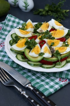 Полезный салат из авокадо, огурцов, яиц и сладкого перца в тарелке на темной поверхности.