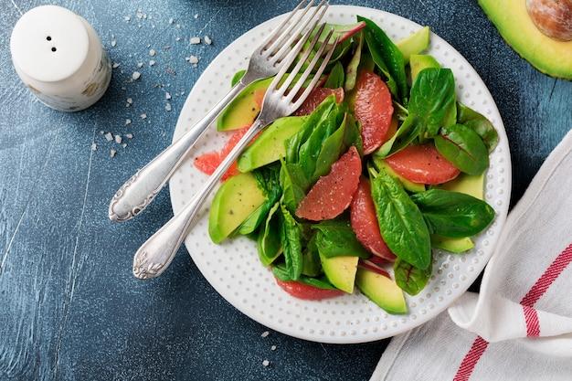 Полезный вкусный салат из шпината, мангольда, авокадо и грейпфрута с оливковым маслом на старой бетонной темной поверхности