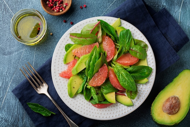 Useful tasty salad of spinach, chard, avocado and grapefruit with olive oil on an old concrete dark background.