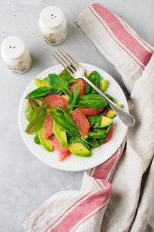 Useful tasty salad of spinach, chard, avocado and grapefruit with olive oil on old concrete gray background.