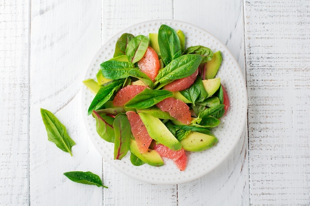 Useful tasty salad of spinach, chard, avocado and grapefruit with olive oil on white wooden rustic background.