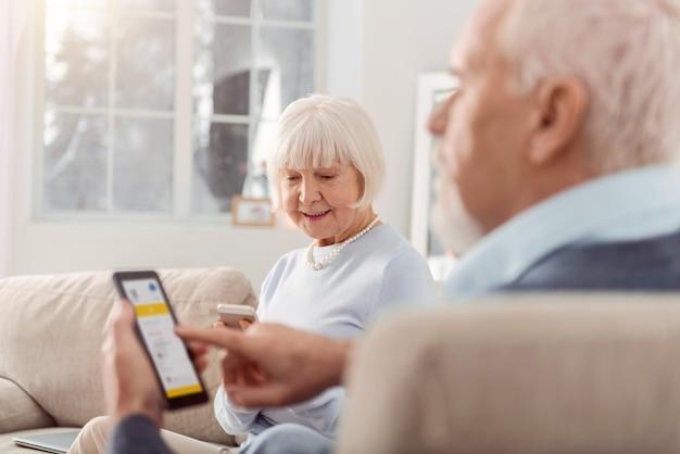 便利なテクノロジー。居間に座って、アプリケーションを使用しながら携帯電話に集中している楽しい老夫婦