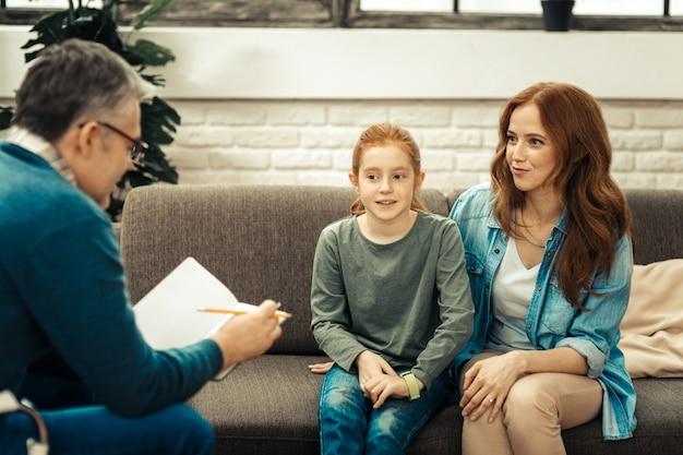 有用な治療法。心理学者を見ながら娘と一緒に座っている素敵なうれしそうな女性