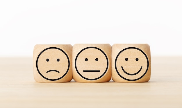 ユーザーサービスのフィードバック、顧客レビューの評価、投票、満足度調査の概念。表情のある木製ブロック