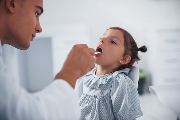 목구멍을 확인하기 위해 편도선을 사용합니다. 젊은 소아과 의사는 진료소에서 작은 여성 방문자와 함께 일합니다.
