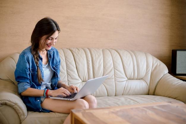 革のソファの上の魅力的な女性usigラップトップ