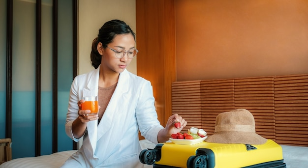 Usinesswoman eating fruits and drink orange juice on bed in luxury hotel room healthy food concept