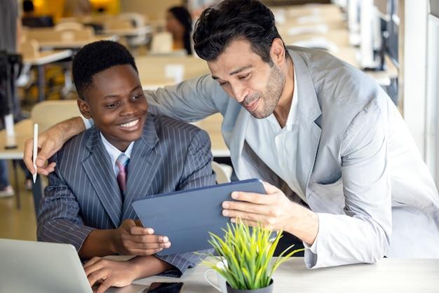 Используя планшетный компьютер, сосредоточенные черно-белые партнеры обсуждают проект. два многорасовых мужчин-партнеров по бизнесу