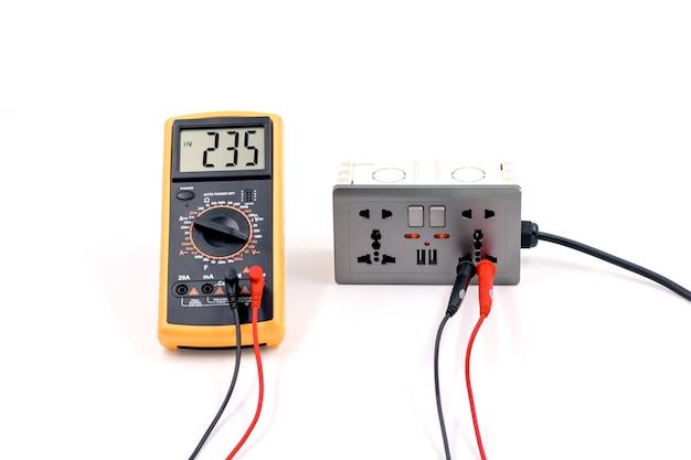 デジタルメーターを使用して、白い背景のコンセントボックスの電圧を測定します。