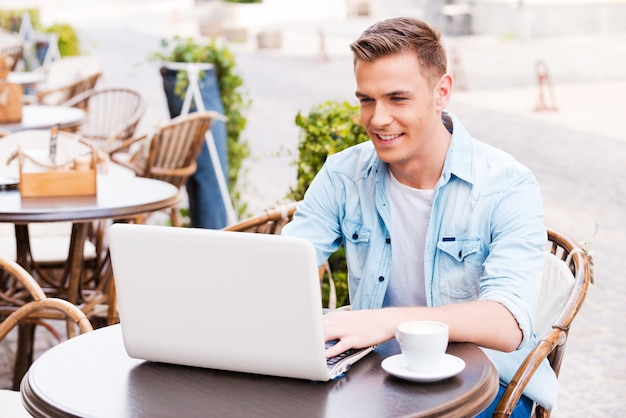 Using advantages of free wi-fi. handsome young man working on laptop and smiling while sitting in sidewalk cafe