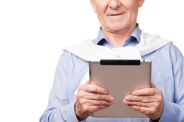 디지털 시대의 장점을 활용합니다. 흰색 배경에 서 있는 동안 디지털 태블릿을 들고 있는 행복한 노인의 자른 이미지