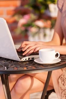 무료 wi-fi의 장점을 사용합니다. 야외 카페에 앉아 노트북 작업을 하는 여성의 자른 이미지