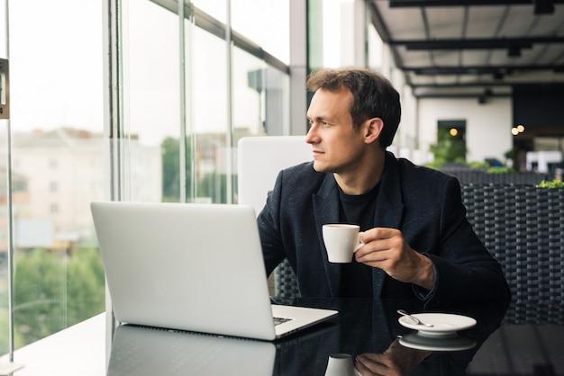 무료 wi-fi의 장점을 사용합니다. 노트북에서 작업하고 보도 카페에 앉아있는 동안 웃 고 잘 생긴 젊은 남자