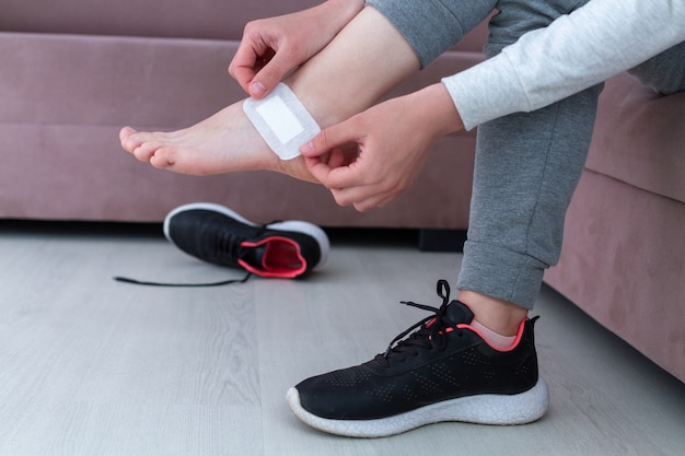 Using bactericidal medical adhesive plaster at home during wearing new shoe. first band aid