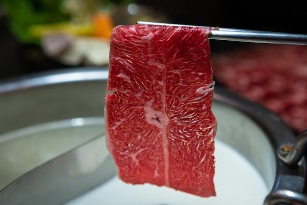中華鍋汁でお箸を使って肉を調理します。ビュッフェレストランで生の新鮮でおいしい豚肉と牛肉のプレート。台湾の代表的な鍋料理