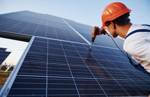 コードレスドライバーを使用します。晴れた日に太陽電池で屋外の青い制服を着た男性労働者。