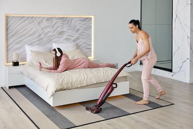 Мама убирает в спальне с помощью беспроводного пылесоса, пока дочь слушает музыку.
