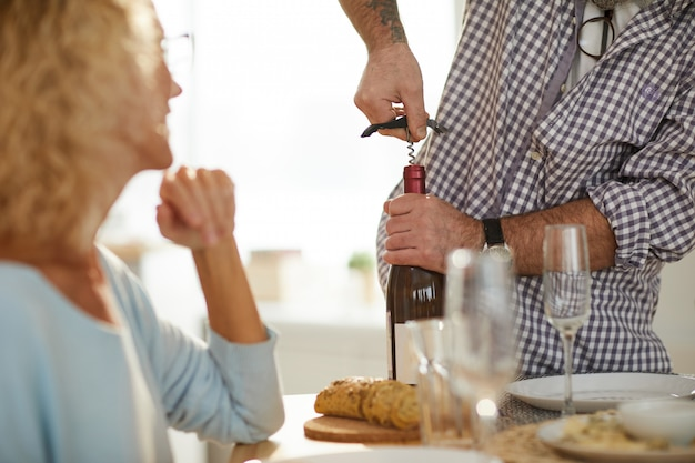 Using corkscrew to open wine bottle