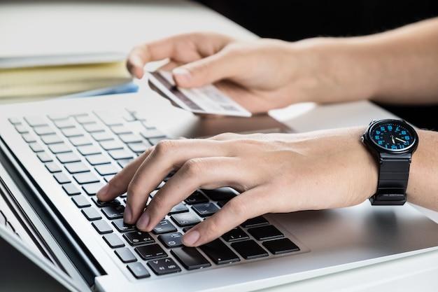 オンライン決済にクレジットカードを使用する。インターネットで何かを購入しながら銀行口座情報を入力する人
